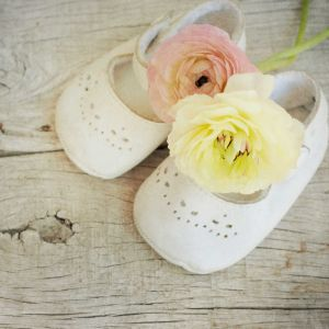 ranunculus flowers bouquet in baby shoes
