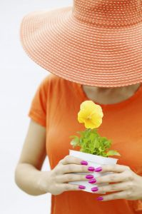 Woman with a potted plant and a sunhat